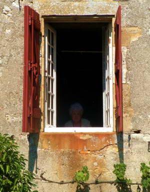 קשישה צופה בנו מאחד הבתים וקפלה בכנסייה המקומית של לוברזאק