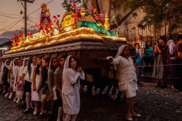 נערות צעירות נושאות מזבח גדול ועליו דמותה של הבתולה מריה, אנטיגואה גואטמלה