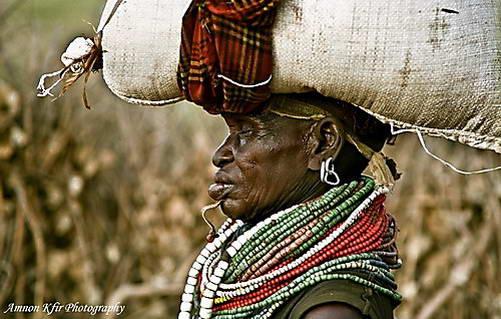 אישה משבט ניאנגטום מאופיינת בסליל מתכת מעוצב הנעוץ בסנטרה ושרשראות צבעוניות על צווארה