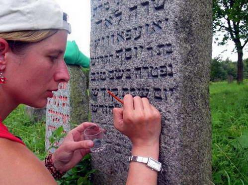 ריטה צובעת את האותיות על מצבה בבית הקברות היהודי בעיירה יורבורג